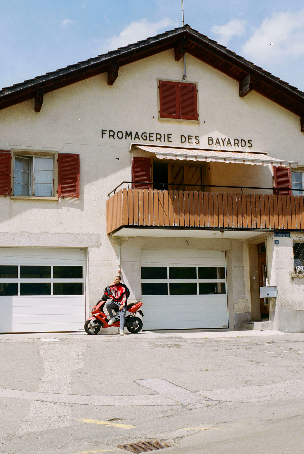 "An image from the collection ""CH 2127 Les Bayards"" by Bryan Colò, who takes a satirical angle to talk about his origins. Here, the model is shot in front of the local dairy - © Photograph: Cynthia Mai Amman, Swiss Design Awards Blog"